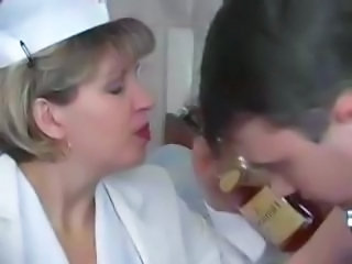 Naughty blonde granny nurse takes a nip from the bottle and his boner