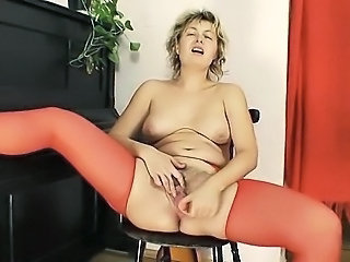 Mature Milf in red stockings grabs a big dildo and starts