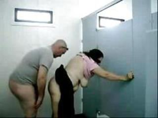Old dude fucks this chubby busty granny in a public toilet